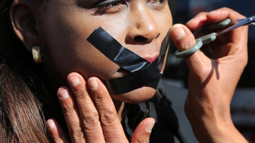 A protester has her lips taped in Johannesburg, Friday July 1, 2016, as journalists and members of the public demonstrate outside the South African Broadcasting Corporation (SABC) headquarters in solidarity with three SABC journalists who were suspended for expressing their concerns about editorial policy amid allegations of newsroom censorship. (AP Photo/Denis Farrell) .