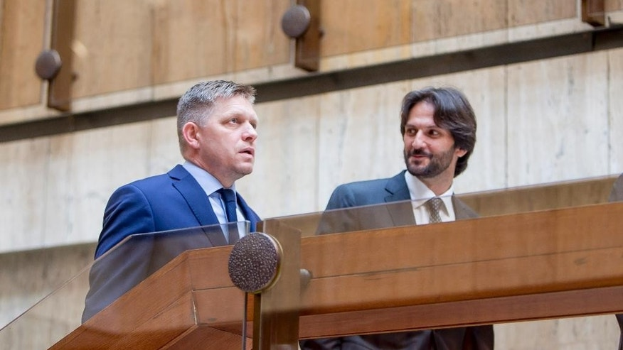 Slovakia's Prime Minister Robert Fico, left, talks to ministry of Interior Robert Kalinak, right, prior a government meeting in Bratislava, Slovakia, Thursday, June 30, 2016.  Slovakia will undertake their six-month presidency of the European Union from July  2016. (AP Photo/Bundas Engler)