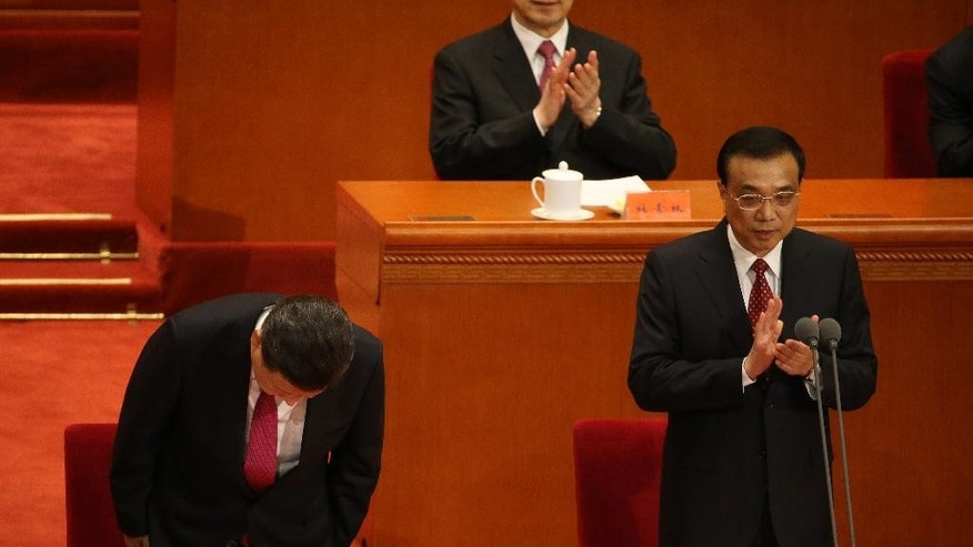 Chinese President Xi Jinping, left, bows as Premier Li Keqiang claps during a ceremony to mark the 95th anniversary of the founding of the Communist Party of China at the Great Hall of the People in Beijing, Friday, July 1, 2016. (How Hwee Young/Pool Photo via AP)