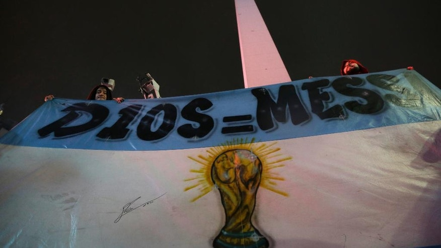 """Lionel Messi fans hold a flag that reads in Spanish """"Messi equals God"""" as they gather to show him their support at the obelisk in Buenos Aires, Argentina, Saturday, July 2, 2016. The rally was organized through social media after Messi announced he's quitting Argentina's national soccer team. (AP Photo/Natacha Pisarenko)"""