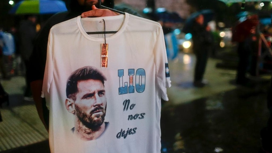 """A vendor holds up a T-shirt that reads in Spanish """"Lio don't leave us"""" at the obelisk where Lionel Messi fans gather to show him their support in Buenos Aires, Argentina, Saturday, July 2, 2016. The rally was organized through social media after Messi announced he's quitting Argentina's national soccer team. (AP Photo/Natacha Pisarenko)"""