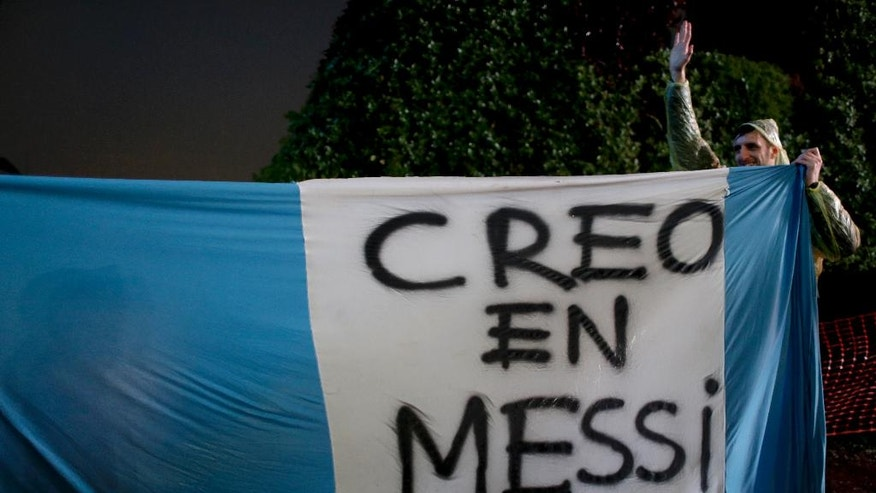 """A fan of Lionel Messi holds a flag that reads in Spanish """"I Believe in Messi"""" during a rally to show Messi their support in Buenos Aires, Argentina, Saturday, July 2, 2016. The rally was organized through social media after Messi announced he's quitting Argentina's national soccer team. (AP Photo/Natacha Pisarenko)"""