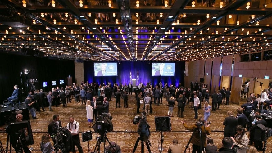 A small group of supporters and media wait for the arrival of Australian Prime Minister, Malcolm Turnbull, to addresses party supporters during a rally in Sydney, Saturday, July 2, 2016, following a general election. The elections, which pit the conservative coalition government against the center-left Labor Party, cap an extraordinarily volatile period in the nation's politics. (AP Photo/Rick Rycroft)