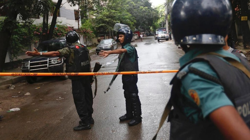 Bangladeshi policemen clear out an area to facilitate action against heavily armed militants who struck at the heart of Bangladesh's diplomatic zone on Friday night, taking dozens of hostages at a restaurant popular with foreigners, Dhaka, Bangladesh, Saturday, July 2, 2016. Police sustained casualties and dozens of people were wounded in a gun battle as security forces cordoned off the area and sought to end the standoff.(AP Photo)