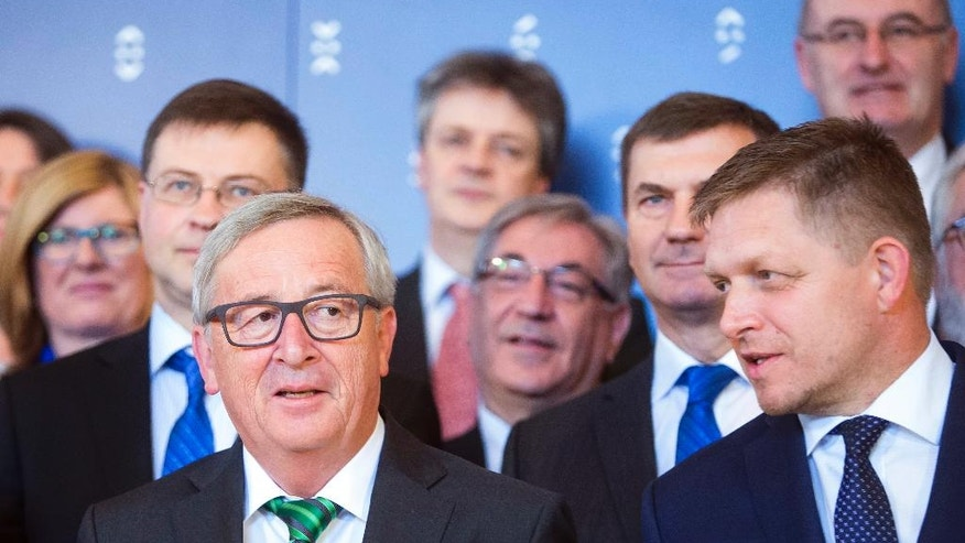The Prime Minister of the Slovak Republic Robert Fico, right,  and the President of the European Commission Jean-Claude Juncker, pose for group photo, with officials after a press conference in Bratislava Friday July 1, 2016.  Slovakia takes over the European Union's presidency on Friday determined to help reconnect the EU with its citizens and put decision-making back in the hands of Europe's nations as the bloc reels from Britain's vote to leave.  (AP Photo/Bundas Engler)