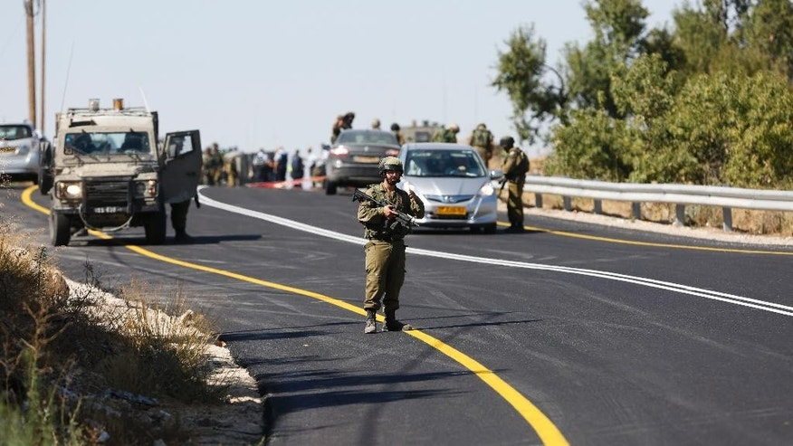 Israeli soldiers secure the scene of a shooting attack near Hebron, West Bank, Friday, July 1, 2016. A Palestinian gunman opened fire at a family traveling in a car in the West Bank on Friday, killing an Israeli man and wounding his wife and two teenage children. (AP Photo/Nasser Shiyoukhi)