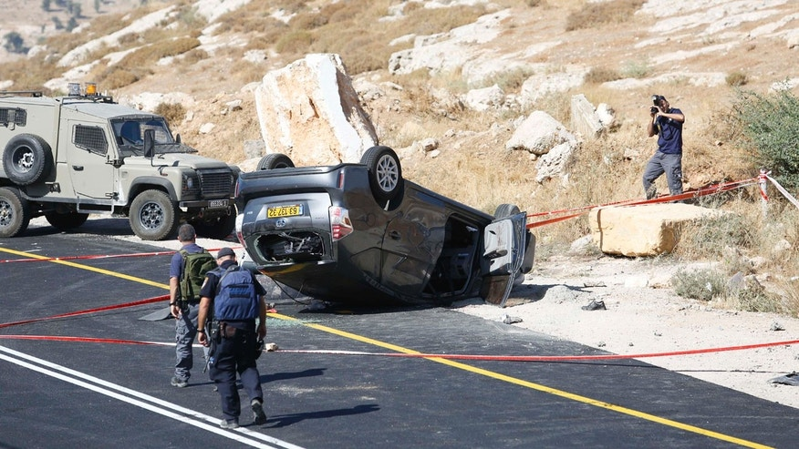 July 1, 2016: Israeli policemen walk at the scene of a shooting attack near Hebron, West Bank. A Palestinian gunman opened fire on a family traveling in a car, killing an Israeli man and wounding his wife and two teenage children.
