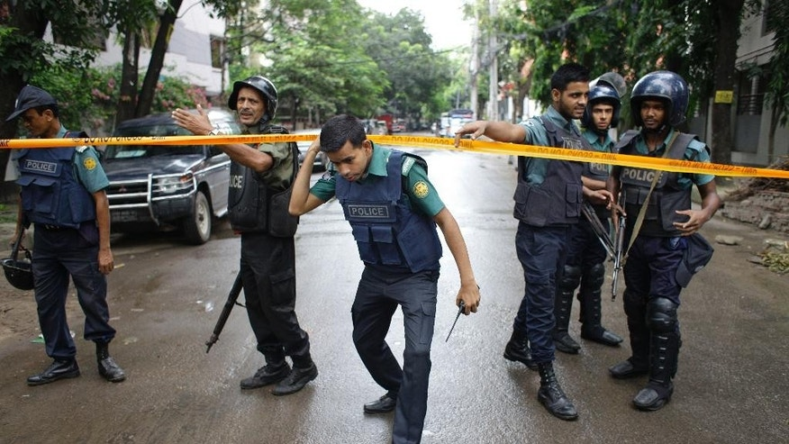 Bangladeshi policemen stand guard in an area cordoned off after heavily armed militants struck at the heart of Bangladesh's diplomatic zone on Friday night, in Dhaka, Bangladesh, Saturday, July 2, 2016. Bangladeshi forces stormed the popular Holey Artisan Bakery in Dhaka's Gulshan area to end a hostage-taking early Saturday. (AP Photo)