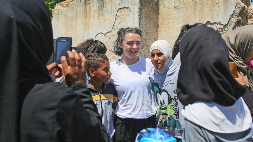 In this Thursday, June 30, 2016, handout photo provided by the International Rescue Committee, actress Maisie Williams, center, poses for a photo with refugee girls in the Cherso refugee camp, northern Greece. Game of Thrones star Maisie Williams traveled to Greece with co-stars in the TV fantasy drama Liam Cunningham and Lena Headey to visit refugee camps with the relief organization, the International Rescue Committee. ( International Rescue Committee via AP)