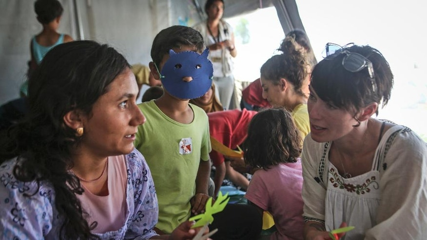In this Thursday, June 30, 2016 handout photo provided by the International Rescue Committee, Lena Headey, right, talks with young Syrian children at Cherso refugee camp in northern Greece. Game of Thrones star Lena Headey traveled to Greece with co-stars in the TV fantasy drama Liam Cunningham and Maisie Williams to visit refugee camps with the relief organization, the International Rescue Committee. (International Rescue Committee via AP)