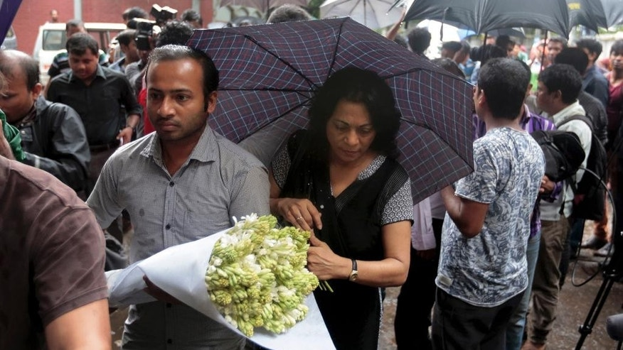 People bring flowers to pay respect to the people who died at Holey Artisan Bakery in Dhaka's Gulshan area, Bangladesh, Sunday, July 3, 2016. The assault on the restaurant in Dhaka's diplomatic zone by militants who took dozens of people hostage marks an escalation in militant violence in the Muslim-majority nation. (AP Photo)