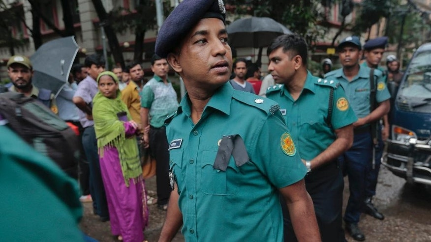 Bangladeshi policemen on duty wear black badges on the first of two days of national mourning for the victims of the attack on the Holey Artisan Bakery in Dhaka, Bangladesh, Sunday, July 3, 2016. The assault on the restaurant in Dhaka's diplomatic zone by militants who took dozens of people hostage marks an escalation in militant violence in the Muslim-majority nation. (AP Photo)