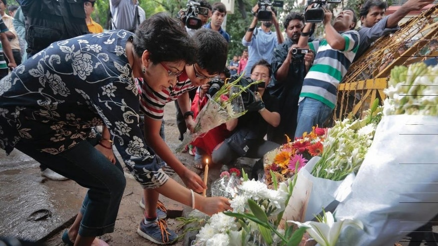 Members of an Indian family offer flowers and light candles as they pay tribute to those killed outside the Holey Artisan Bakery in Dhaka, Bangladesh, Sunday, July 3, 2016. The assault on the restaurant in Dhaka's diplomatic zone by militants who took dozens of people hostage marks an escalation in militant violence in the Muslim-majority nation. (AP Photo)