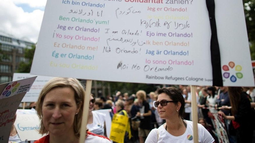 Participants gather for a Christopher Street Day parade in Cologne, western Germany, Sunday July 3, 2016 and hold a poster in different languages reading 'I am Orlando',  to remember the victims of the Orlando nightclub shooting.  ( Maja Hitij/dpa via AP)