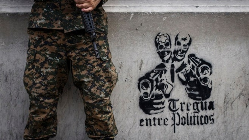 "In this June 14, 2016 photo, a soldier stands next to a stenciled graffiti that reads in Spanish ""Truce between politicians"" painted on the main walls of the National Palace in San Salvador, El Salvador. After becoming the world's murder capital last year and posting an equally bloody start to 2016, El Salvador has seen its monthly homicide rates fall by about half. The government attributes the drop to a tough military crackdown on the country's powerful gangs, while the gangs themselves claim credit for a nonaggression pact between the three biggest criminal groups. (AP Photo/Salvador Melendez)"