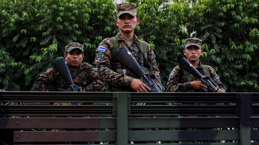 In this June 14, 2016 photo, reserve soldiers stand on a truck during a presentation to the press at the Central Square in San Salvador, El Salvador, as part of extraordinary security measures to dismantle gangs. After becoming the world's murder capital last year and posting an equally bloody start to 2016, El Salvador has seen its monthly homicide rates fall by about half. The government attributes the drop to a tough military crackdown on the country's powerful gangs, while the gangs themselves claim credit for a nonaggression pact between the three biggest criminal groups. (AP Photo/Salvador Melendez)