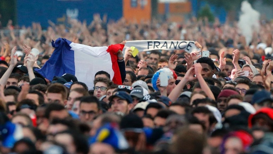 Fans react as they watch the Euro 2016 quarterfinal soccer match between France and Iceland, at the Eiffel Tower fanzone  in Paris, France, Sunday, July 3, 2016. (AP Photo/Francois Mori)
