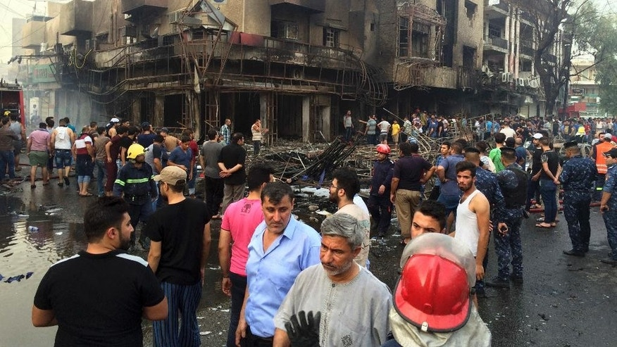 Iraqi security forces and civilians gather at the site after a car bomb at a commercial area in Karada neighborhood, Baghdad, Iraq, Sunday, July 3, 2016. Bombs went off early Sunday in two crowded commercial areas in Baghdad. (AP Photo/Khalid Mohammed)
