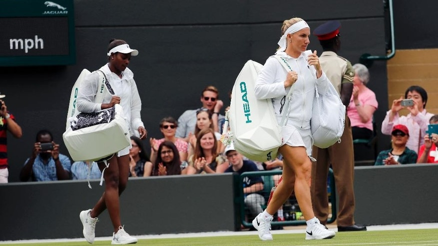 Sloane Stephens of the U.S, right, and Svetlana Kuznetsova of Russia arrive on court for their women's singles match on during day seven of the Wimbledon Tennis Championships in London, Sunday, July 3, 2016. (AP Photo/Ben Curtis)