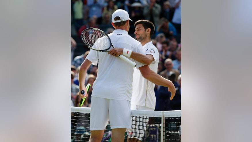 Sam Querrey of the U.S, left, shakes hands with Novak Djokovic of Serbia after beating him in their men's singles match on day six of the Wimbledon Tennis Championships in London, Saturday, July 2, 2016. (AP Photo/Alastair Grant)