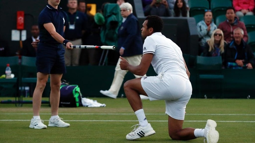Jo-Wilfried Tsonga of France slips over during his men's singles match against John Isner of the U.S on day six of the Wimbledon Tennis Championships in London, Saturday, July 2, 2016. (AP Photo/Alastair Grant)