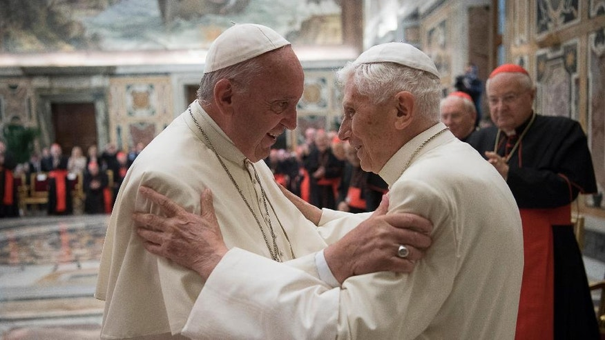 Pope Francis, left, and retired Pope Benedict XVI embrace during a ceremony to celebrate Benedict's 65th anniversary of his ordination as a priest, in the Clementine Hall of the Apostolic Palace, at the Vatican, Tuesday, June 28, 2016. The ceremony served in part to show continuity from Benedict to Francis amid continued nostalgia from some conservatives for Benedict's tradition-minded papacy. (L'Osservatore Romano/Pool photo via AP)