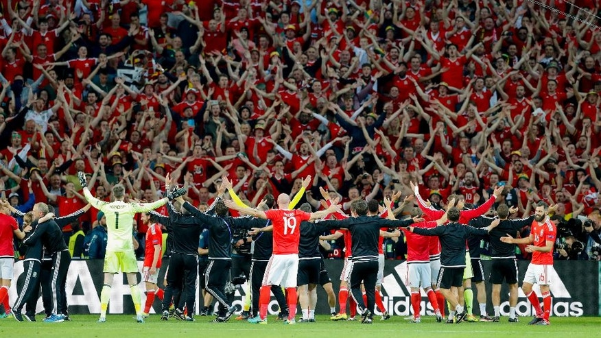 Wales' players celebrate with fans their 3-1 win at the end of the Euro 2016 quarterfinal soccer match between Wales and Belgium, at the Pierre Mauroy stadium in Villeneuve d'Ascq, near Lille, France, Friday, July 1, 2016. (AP Photo/ Michel Spingler)