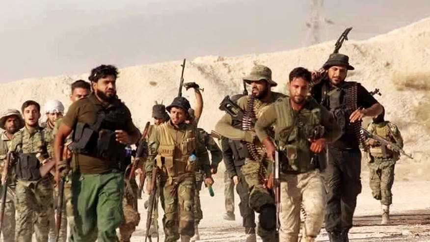 U.S.-backed Syrian rebels of the New Syrian Army march in Syria.
