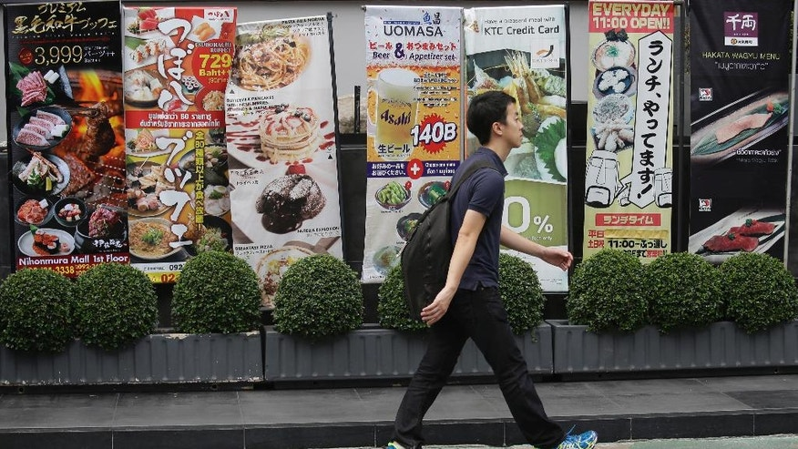 In this June 24, 2016 photo, a pedestrian passes by advertisements for Japanese restaurants in Bangkok, Thailand. Thais admire Japanese craftsmanship and the culture's emphasis on courteous and subdued manners, and tend to look to Japan as a role model. Thailand, meanwhile, is a favored destination for Japanese corporate investment and is seen an inviting tourist spot that's different but not too foreign. The mutual affection between these two nations is rare in Asia, where historical, political and territorial tensions often complicate ties. (AP Photo/Sakchai Lalit)