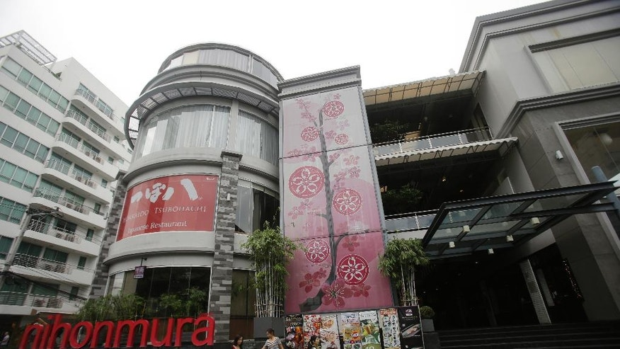 In this June 24, 2016 photo, a Japanese family living in Bangkok walks past Japanese shopping mall in Bangkok, Thailand. Thai admires Japan culture's emphasis on courteous and subdued manners - widespread sentiments among Thais, who look to Japan more than China, the U.S. or other Asian neighbors as an example to follow. The mutual affection between these two nations is rare in Asia, where historical, political and territorial tensions often complicate ties. (AP Photo/Sakchai Lalit)