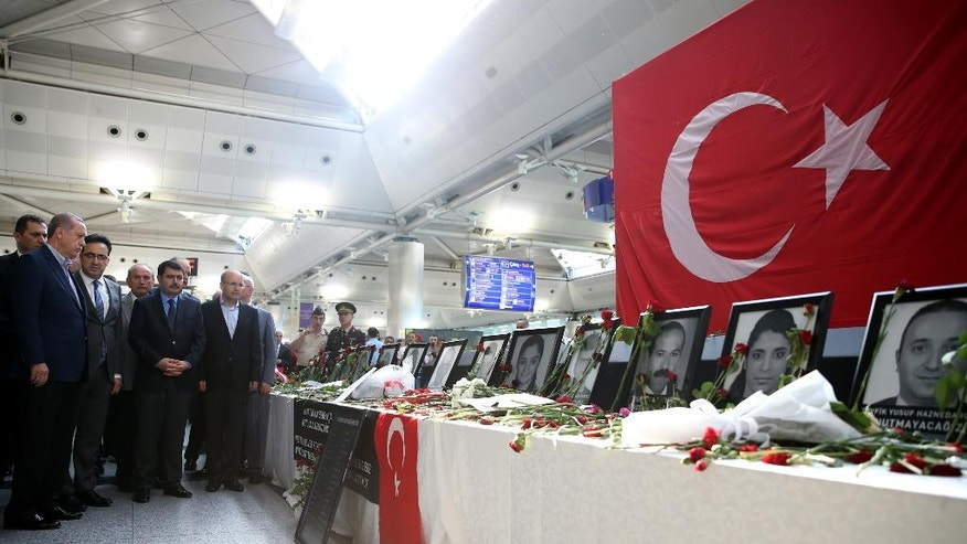 Turkey's President Recep Tayyip Erdogan, left, visits Ataturk Airport in Istanbul, where photographs of Tuesday's blasts' victims are displayed, Saturday, July 2, 2016. Tuesday's gunfire and suicide bombing attack at Ataturk Airport killed dozens and injured over 200. Turkish authorities have banned distribution of images relating to the Ataturk airport attack within Turkey. (Kayhan Ozer, Presidential Press Service, Pool via AP)