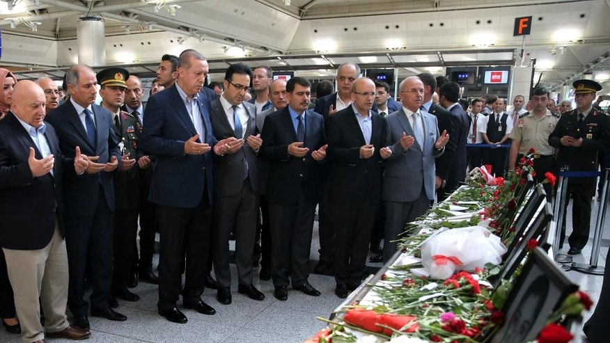 Turkey's President Recep Tayyip Erdogan, third left, prays in front of photographs of Tuesday's blast victims at Ataturk Airport in Istanbul, Saturday, July 2, 2016. Tuesday's gunfire and suicide bombing attack at Ataturk Airport killed dozens and injured over 200. Turkish authorities have banned distribution of images relating to the Ataturk airport attack within Turkey. (Kayhan Ozer, Presidential Press Service, Pool via AP)