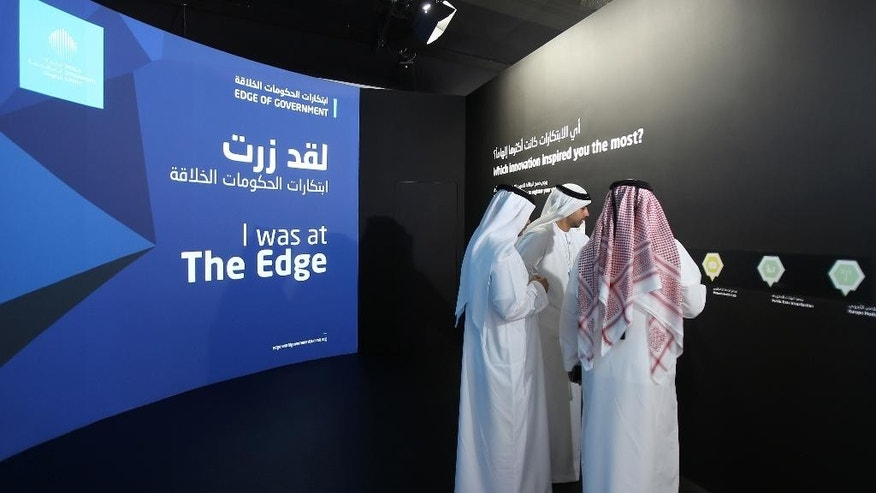 FILE -- In this Feb. 8, 2016 file photo, Emirati officials visit an exhibition at the World Government Summit in Dubai, United Arab Emirates. In a tweet late Saturday, July 2, 2016 from the Ministry of Foreign Affairs  warned its citizens to avoid wearing traditional garments when traveling abroad after an Emirati man was handcuffed last week in Ohio over terrorism fears. Local media reported Sunday that Emirati national Ahmed al-Menhali was detained at gunpoint last week while wearing a traditional white kandura, or ankle-length robe, and headscarf in Avon, Ohio after a hotel clerk raised suspicions he could have links to the Islamic State group. (AP Photo/Kamran Jebreili)