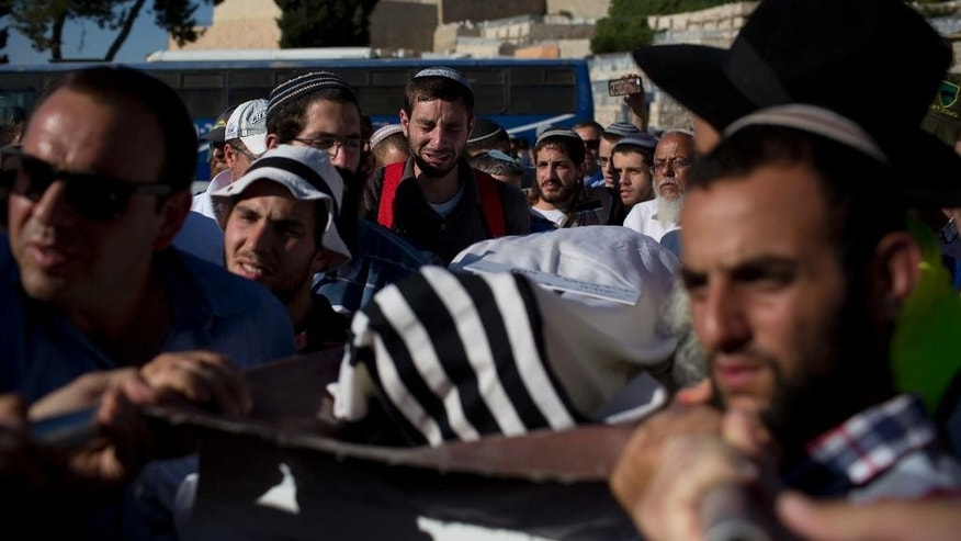 Mourners carry the body of Miki Mark who was killed in an shooting attack in the West Bank Friday, during his funeral in Jerusalem Sunday, July 3, 2016. Mark was killed by Palestinian gunman while driving his family near Hebron. His wife and two teenage daughters were wounded in the attack. (AP Photo/Oded Balilty)