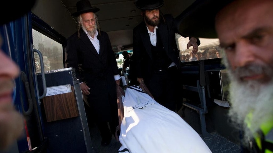 Mourners stand by the body of Miki Mark who was killed in an shooting attack in the West Bank Friday, during his funeral in Jerusalem Sunday, July 3, 2016. Mark was killed by Palestinian gunman while driving his family near Hebron. His wife and two teenage daughters were wounded in the attack. (AP Photo/Oded Balilty)