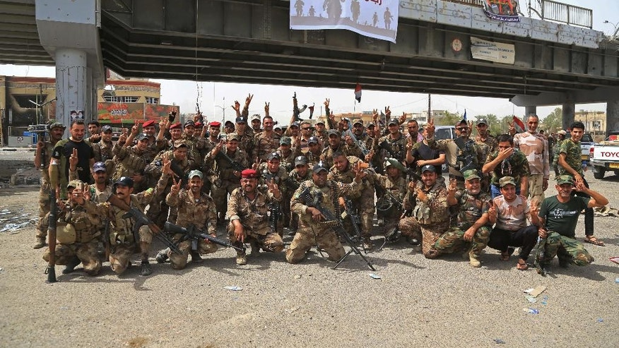 In this Thursday, June 28, 2016 photo, Iraqi security forces celebrate their victory in Fallujah, Iraq. In the newly-liberated Sunni city of Fallujah, the proliferation of Shiite militia flags and graffiti has the potential to undermine military successes and hamper the broader fight against the Islamic State group by reigniting the sectarian tensions that fueled the militants' rise in Iraq. (AP Photo/Karim Kadim)