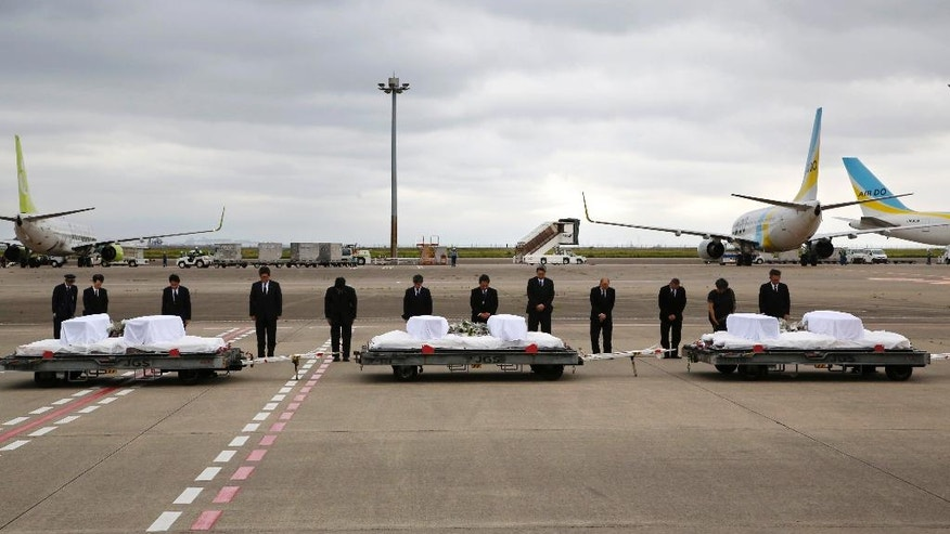 Japanese Foreign Minister Fumio Kishida, third left, with other officials, bows in front of the coffins of the victims who were killed in the last weekend's attack on a restaurant in Bangladeshi capital Dhaka, at Haneda Airport in Tokyo, Tuesday, July 5, 2016. The bodies of the Japanese victims arrived Tuesday morning in Tokyo on a Japanese government airplane. (AP Photo/Shizuo Kambayashi)