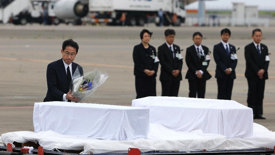 Japanese Foreign Minister Fumio Kishida, left, lays flowers on the coffins of the victims who were killed in the last weekend's attack on a restaurant in Bangladeshi capital Dhaka, at Haneda Airport in Tokyo, Tuesday, July 5, 2016. The bodies of the Japanese victims arrived Tuesday morning in Tokyo on a Japanese government airplane. (AP Photo/Shizuo Kambayashi)