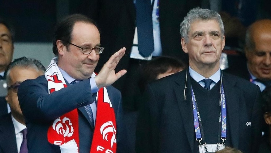French President Francois Hollande waves as he stands beside UEFA vice-president Angel Villar Llona prior to the Euro 2016 quarterfinal soccer match between France and Iceland, at the Stade de France in Saint-Denis, north of Paris, France, Sunday, July 3, 2016. (AP Photo/Frank Augstein)