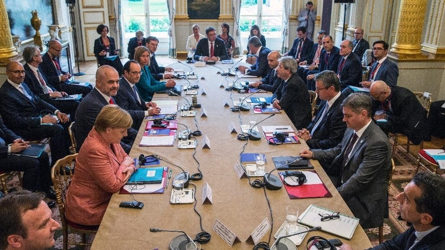 Delegations from the Balkans sit around a table around French President Francois Hollande, fourth from left, and German Chancellor Angela Merkel, second from left, during the Balkan summit hosted by France at the Elysee Palace in Paris, Monday July 4, 2016. The leaders of France, Germany, Italy and Balkan nations are meeting to better prevent extremists from sneaking in with migrants who are moving west across Europe. (Etienne Laurent, Pool via AP)