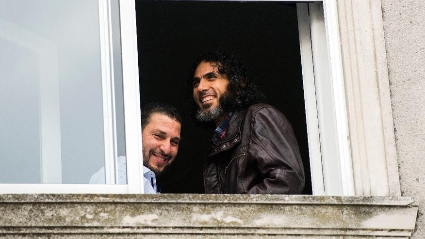 FILE - In this June 5, 2015 file photo, Abu Wa'el Dhiab, from Syria, right, and Adel bin Muhammad El Ouerghi, of Tunisia, both freed Guantanamo Bay detainees, stand next to the window of their shared home in Montevideo, Uruguay. A Brazilian airline is asking its employees to be on the lookout for Abu Wa'el Dhiab, who was resettled in Uruguay and is supposed to have traveled to Brazil,  Avianca Airlines spokesman Danilo Alves said on Monday, July 4, 2016. (AP Photo/Matilde Campodonico, File)