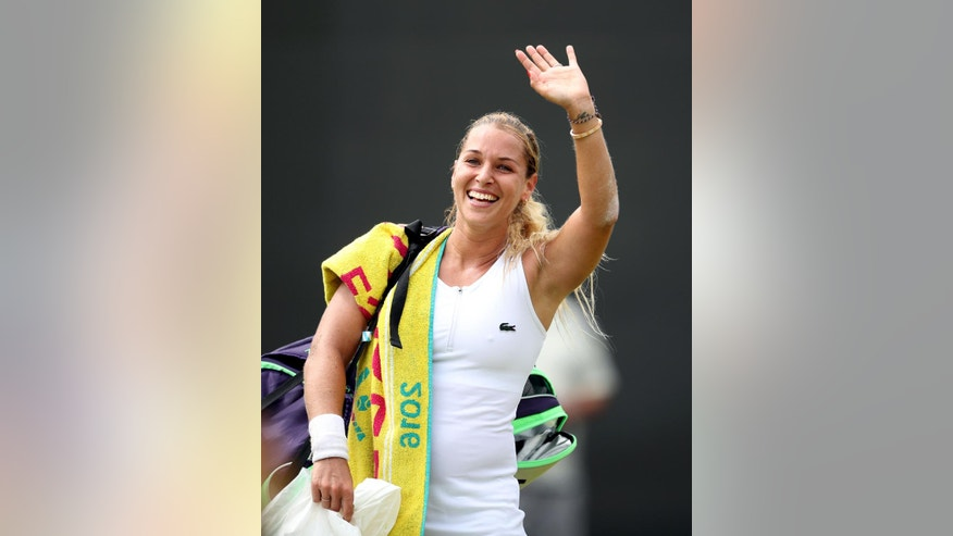 Dominika Cibulkova of Slovakia celebrates after beating Agnieszka Radwanska of Poland during their women's singles match on day eight of the Wimbledon Tennis Championships in London, Monday, July 4, 2016. (Anthony Devlin PA via AP)