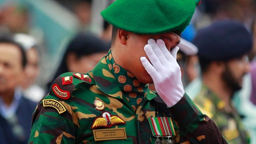 A Bangladeshi soldier reacts as people pay their respects to the Bangladeshi victims of the attack on Holey Artisan Bakery, at a stadium in Dhaka, Bangladesh, Monday, July 4, 2016. The brutality of the attack, the worst convulsion of violence yet in the recent series of deadly attacks to hit Bangladesh, has stunned the traditionally moderate Muslim nation and raised global concerns about whether it can cope with the increasingly strident Islamist militants. (AP Photo)