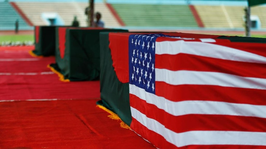Coffins bearing the bodies of victims of the attack on the Holey Artisan Bakery – one draped in both the Bangladesh and U.S. flags – are laid out for people to pay their last respects, at a stadium in Dhaka, Bangladesh, Monday, July 4, 2016. The brutality of the attack, the worst convulsion of violence yet in the recent series of deadly attacks to hit Bangladesh, has stunned the traditionally moderate Muslim nation and raised global concerns about whether it can cope with the increasingly strident Islamist militants. (AP Photo)