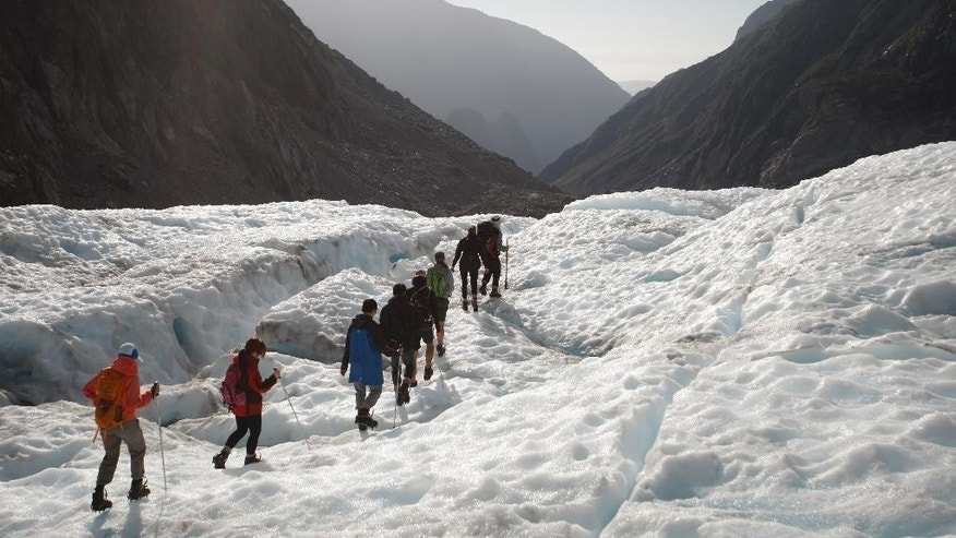 FILE - In this Feb. 6, 2016 file photo, tourist relax at the end of the track at the Fox Glacier in New Zealand. Ski fields are struggling to open and winter electricity consumption is down in New Zealand after the first six months of 2016 proved to be the hottest start to a year that scientists have ever recorded. Temperatures in the South Pacific nation were 1.4 degrees Celsius (2.5 Fahrenheit) above the long-term average for the first half of the year, according to the government-funded National Institute of Water and Atmospheric Research.(AP Photo/Nick Perry)