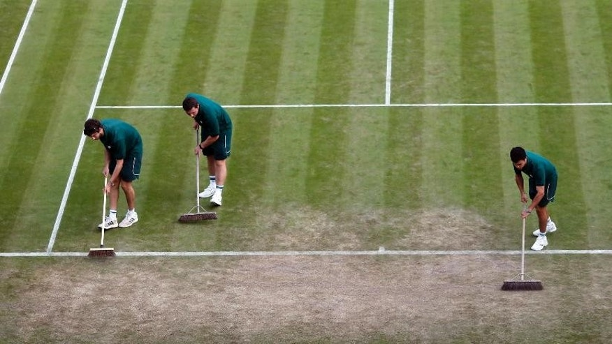 Ground staff sweep the baseline during day seven of the Wimbledon Tennis Championships in London, Sunday, July 3, 2016. (AP Photo/Ben Curtis)