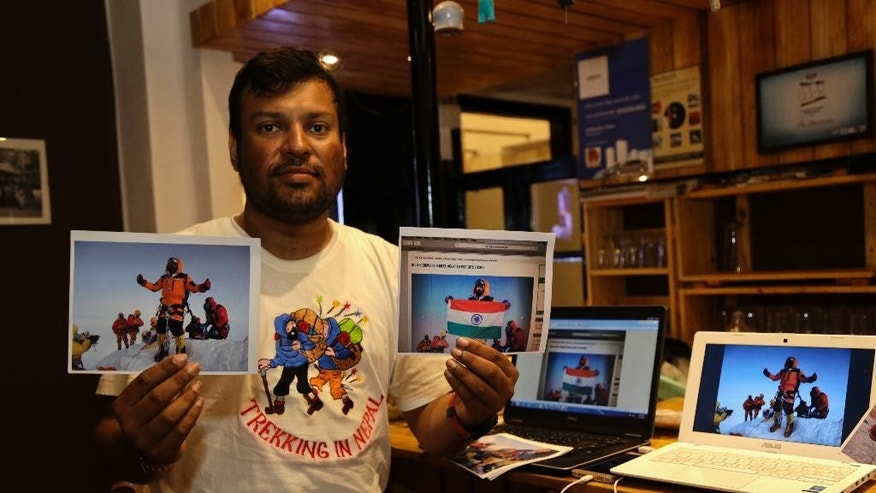 Indian climber, Satyarup Sidhantha holds on his right hand a photograph that shows him on Mount Everest, along with what he says is an altered version of the same used by an Indian couple to make it appear they were on the summit, as he displays them for the Associated Press in Kolkata, India, Monday, July 4, 2016. Nepal's mountaineering authorities are investigating a climbing claim by an Indian couple who are accused of altering photographs of themselves on the summit of Mount Everest, an official said Monday. (AP Photo/ Bikas Das)