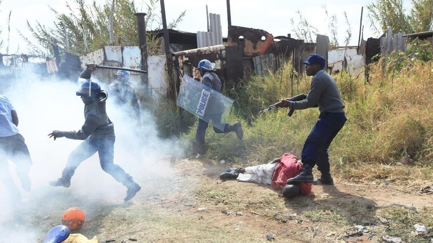 Armed Zimbabwean police battle rioters in Harare, Monday, July, 4, 2016. Police in Zimbabwe's capital fired tear gas and water cannons in an attempt to quell rioting by taxi and mini bus drivers protesting what they describe as police harassment.The violence came amid a surge in protests in recent weeks because of economic hardships and alleged mismanagement by the government of President Robert Mugabe.(AP Photo/Tsvangirayi Mukwazhi)