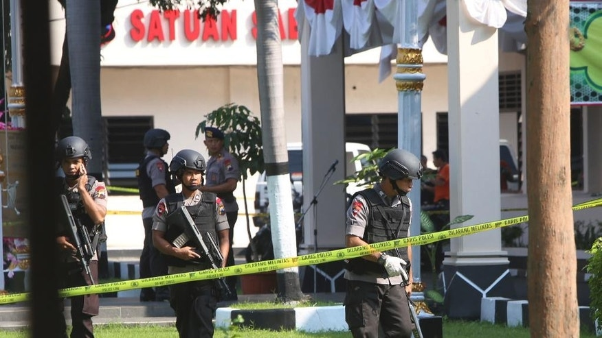 Members of police bomb squad examine the surrounding area near where a suicide bomber blew himself up at the local police headquarters in Solo, Central Java, Indonesia, Tuesday, July 5, 2016. Local authorities believed the attack was carried out by a militant network that targets police and other security forces, Chief of Central Java Police Maj. Gen. Condro Kirono said. (AP Photo)