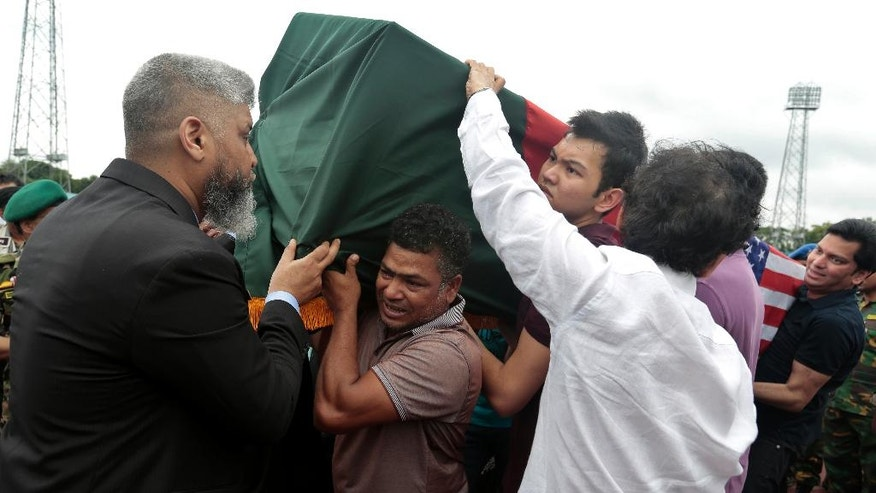 A coffin bearing the body of a Bangladeshi victim of the attack on Holey Artisan Bakery, draped in national flag, is brought in for a ceremony for people to pay their tribute, at a stadium in Dhaka, Bangladesh, Monday, July 4, 2016. The assault on the restaurant in Dhaka's diplomatic zone by militants who took dozens of people hostage marked an escalation in militant violence in the Muslim-majority nation. (AP Photo)